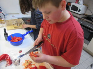 Jede/Jeder trägt seinen Teil der Vorbereitung zum Essen bei. Geteilte Arbeit in der Küche, ist gemeinsame Freue beim Essen. So wie auf diesem Bild.